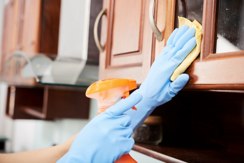 A person with blue gloves cleaning the kitchen cabinet with a yellow wipes and orange spray bottle.